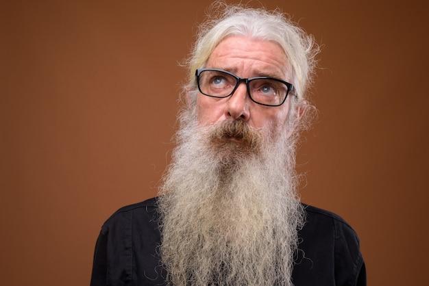 Ritratto di uomo barbuto senior pensando e guardando in alto