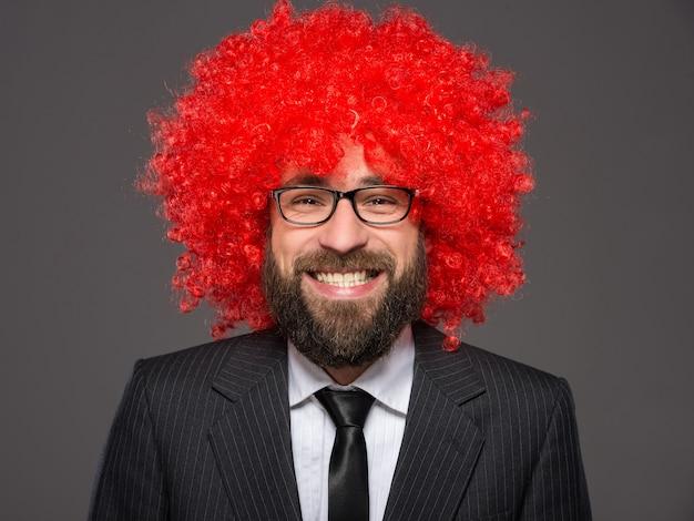 Ritratto di uomo barbuto sorridente in una tuta e una parrucca rossa.