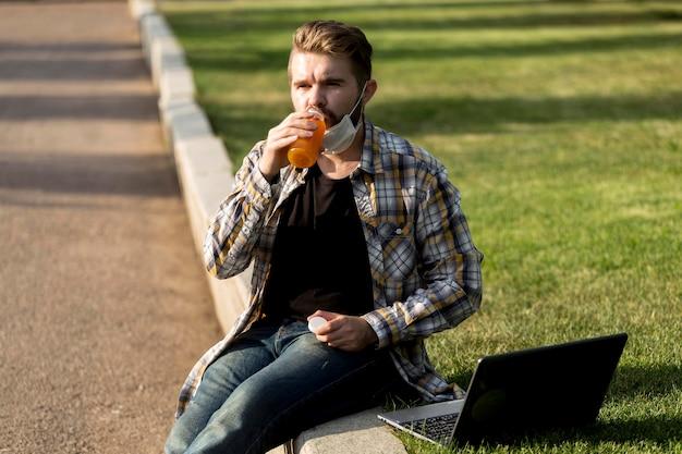 Ritratto di uomo bello che beve succo di frutta