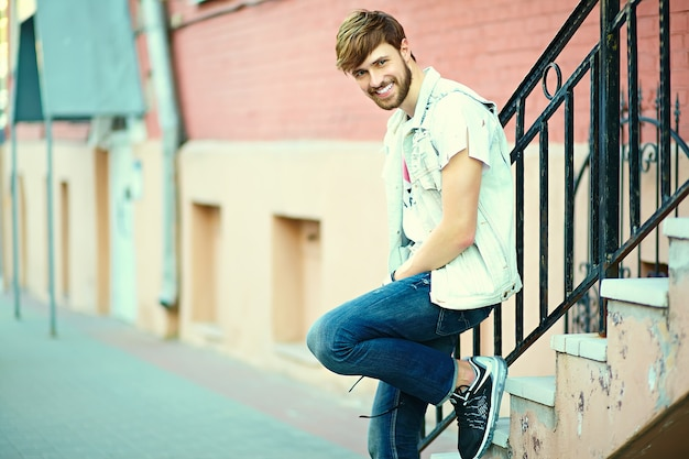 Ritratto di uomo bello in abiti eleganti hipster. ragazzo attraente in posa in strada