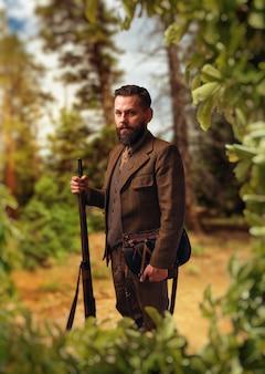 Ritratto di uomo cacciatore impanato in abiti da caccia tradizionali con il vecchio fucile sulla foresta verde