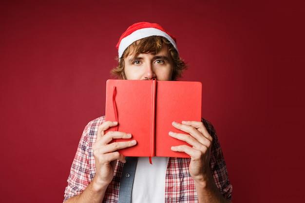 Ritratto di uomo carino nascosto dietro il libro