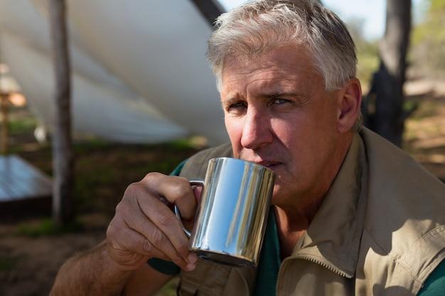 Ritratto di uomo che beve il caffè in campeggio