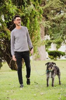 Ritratto di uomo che cammina con il suo cane sull'erba verde nel parco