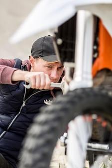 Ritratto di uomo che cerca di riparare la moto