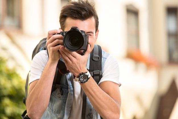 Ritratto di uomo che tiene la fotocamera digitale.