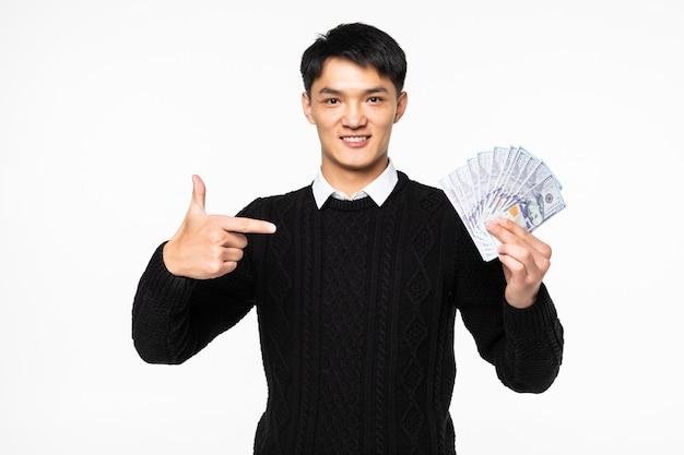 Ritratto di uomo cinese eccitato pointe su molte banconote isolate sul muro bianco