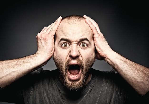 Ritratto di uomo con espressioni sorprese tenendo la testa con le mani