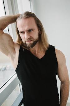 Ritratto di uomo con lunghi capelli biondi guardando a porte chiuse. ritratto del primo piano di giovane ragazzo che posa nel bianco. toro brutale con incredibili occhi toccano i capelli