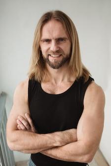 Ritratto di uomo con lunghi capelli biondi. ritratto del primo piano di giovane ragazzo. toro brutale con occhi incredibili e denti bianchi che sorridono