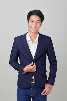 Ritratto di uomo d'affari asiatico alla moda su grigio brillante