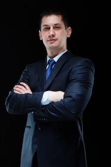 Ritratto di uomo d'affari bello fiducioso con le braccia incrociate