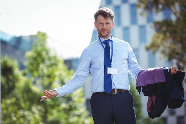Ritratto di uomo d'affari bello in piedi con giacca sportiva
