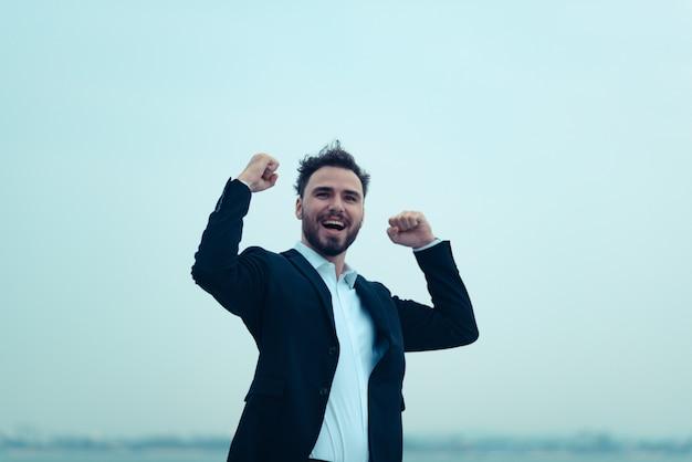 Ritratto di uomo d'affari di giovane elegante uomo sorridente in tuta in posa su un yacht
