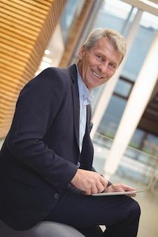 Ritratto di uomo d'affari felice utilizzando la tavoletta digitale