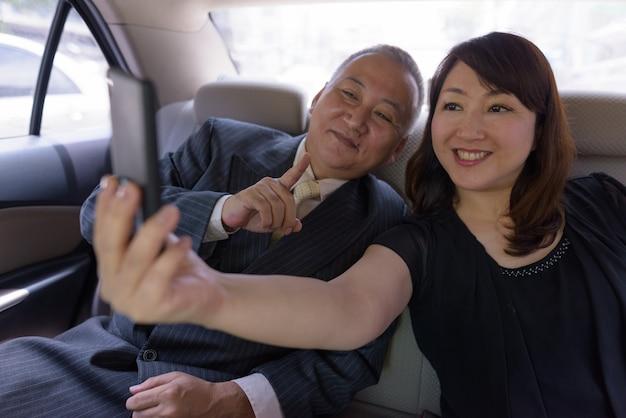 Ritratto di uomo d'affari giapponese maturo e donna giapponese matura esplorare la città di bangkok