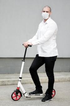 Ritratto di uomo d'affari in posa con scooter