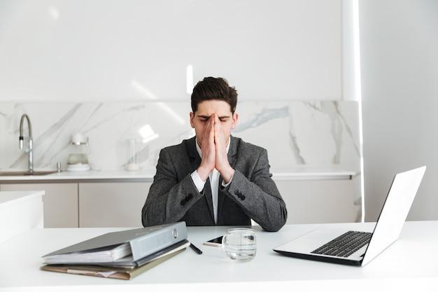 Ritratto di uomo d'affari stanco che copre il viso con le mani mentre lavora troppo e seduto al tavolo in ufficio, con gli occhi chiusi