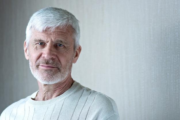 Ritratto di uomo dai capelli grigi in abiti leggeri e occhiali