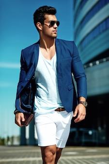 Ritratto di uomo di modello maschio sexy moda bello vestito in abito elegante in posa sulla strada. cielo blu