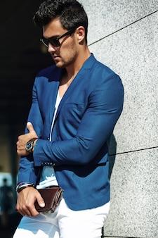 Ritratto di uomo di modello maschio sexy moda bello vestito in abito elegante in posa sullo sfondo strada
