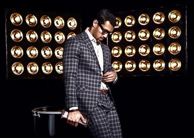 Ritratto di uomo di modello maschio sexy moda bello vestito in abito elegante su sfondo di luci di studio