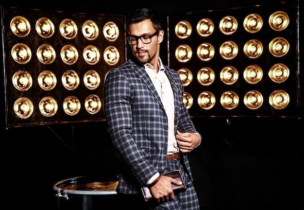 Ritratto di uomo di modello maschio sexy moda bello vestito in abito elegante su sfondo nero luci studio in bicchieri