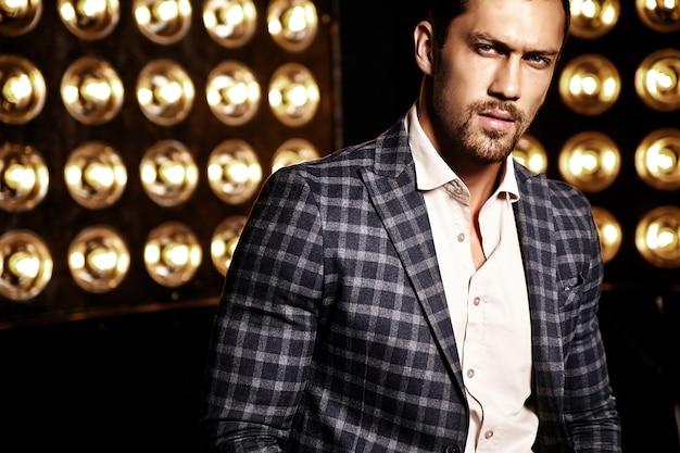 Ritratto di uomo di modello maschio sexy moda bello vestito in abito elegante su sfondo nero luci studio