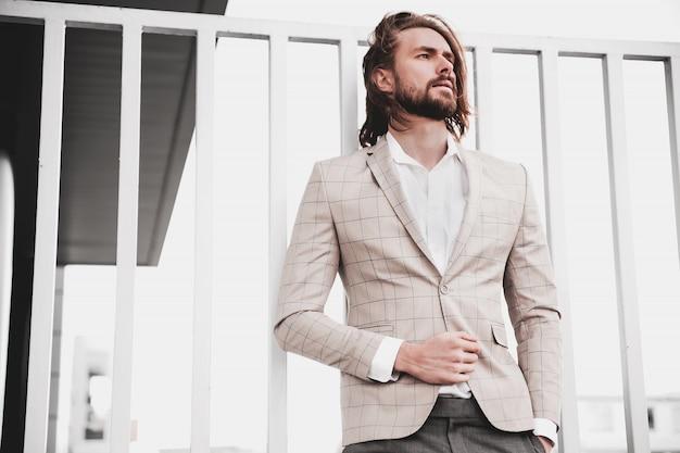 Ritratto di uomo di modello maschio sexy moda bello vestito in elegante abito a scacchi beige in posa sullo sfondo strada