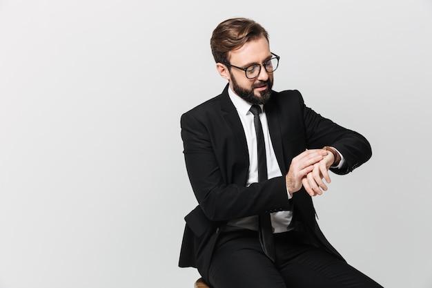 Ritratto di uomo di successo in tuta e occhiali seduto sulla sedia e guardare l'orologio, isolato su muro bianco