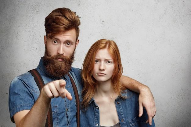 Ritratto di uomo dispiaciuto o arrabbiato con barba elegante che punta e abbraccia una bella donna dai capelli rossi in modo protettivo con sguardo ferito, difendendo la sua ragazza e avvertendoti di non toccarla