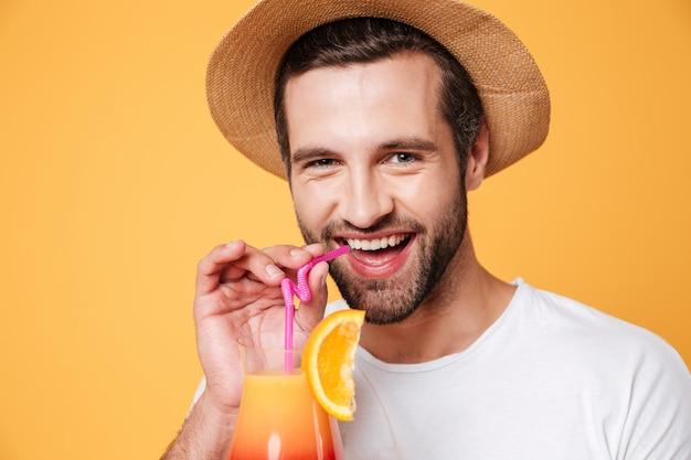 Ritratto di uomo divertente che tiene cocktail vicino alla bocca