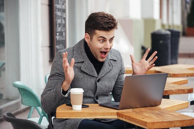 Ritratto di uomo eccitato sorpreso emotivamente guardando nel computer portatile d'argento, urlando e gioendo