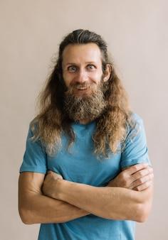 Ritratto di uomo emotivo divertente con barba, baffi, capelli lunghi, guardando la fotocamera e sorridente, sfondo isolato