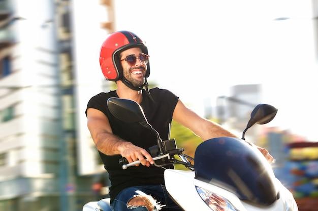 Ritratto di uomo felice con il casco in giro in moto in città