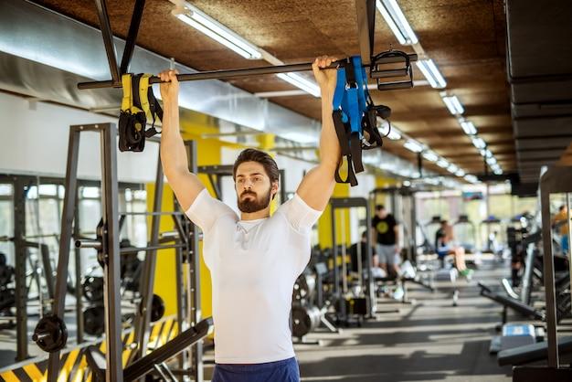 Ritratto di uomo forte di forma muscolare attraente che tiene la barra sopra la testa e sollevando nella soleggiata palestra moderna.