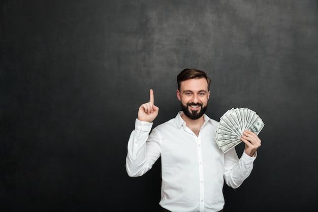 Ritratto di uomo fortunato in camicia bianca con in mano un sacco di soldi in contanti e mostrando il dito su grigio scuro