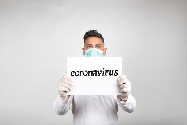 Ritratto di uomo in maschera chirurgica con un cartello bianco con la parola coronavirus su sfondo bianco.