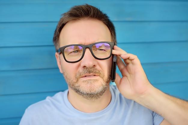 Ritratto di uomo maturo bello parlare al telefono.