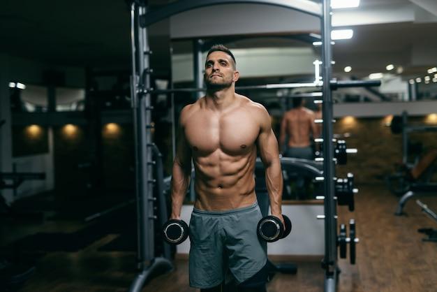 Ritratto di uomo muscoloso torso nudo in piedi e in possesso di manubri in mano