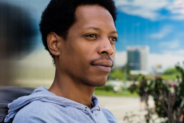 Ritratto di uomo nero in fondo urbano.