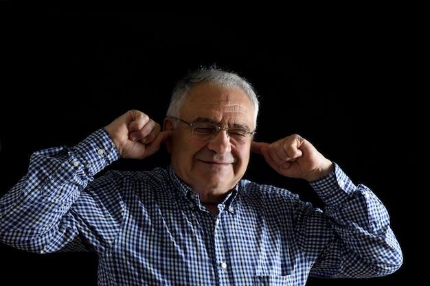 Ritratto di uomo pensionato con rumoroso sul nero