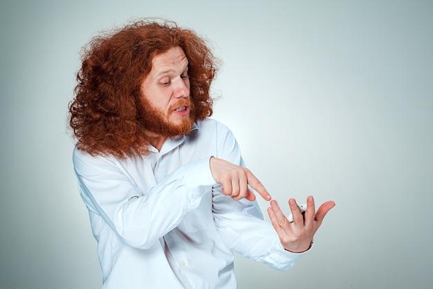 Ritratto di uomo perplesso con lunghi capelli rossi su sfondo grigio