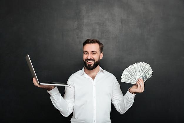 Ritratto di uomo ricco allegro in camicia bianca che vince un sacco di valuta del dollaro dei soldi usando il suo taccuino sopra grigio scuro