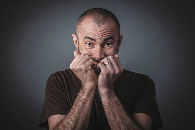 Ritratto di uomo spaventato con le mani chiuse giunte vicino alla bocca.