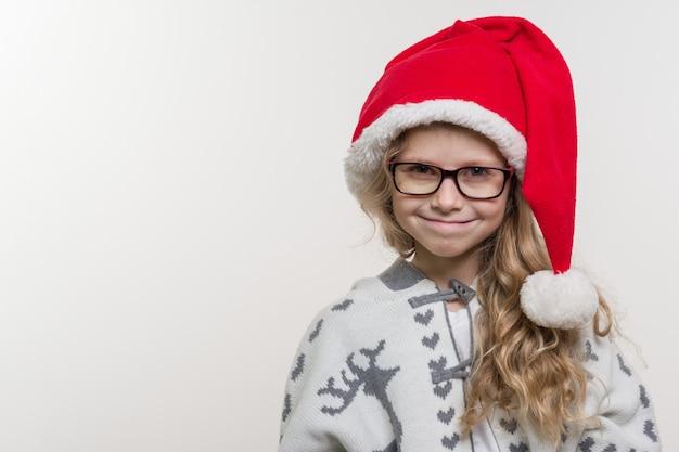 Ritratto di vacanze invernali della ragazza divertente in cappello di babbo natale