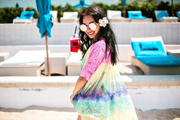 Ritratto di vacanze positive estive di donna bella mora divertendosi al beach club di lusso, corpo sottile, bikini alla moda e kimono, tenendo la bevanda analcolica.