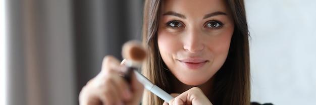 Ritratto di visagist che guarda l'obbiettivo con timidezza e gioia. sorridente truccatore che utilizza strumenti speciali e professionali. concetto di bellezza e maquillage