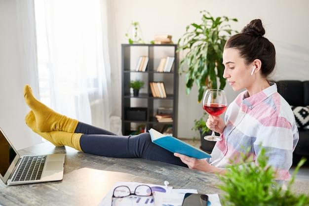 Ritratto di vista laterale del libro di lettura rilassato della giovane donna e del vino bevente con i piedi sullo scrittorio, spazio della copia
