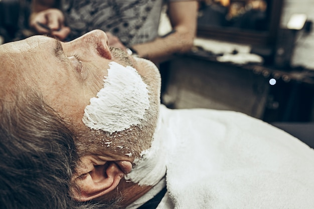 Ritratto di vista laterale del primo piano dell'uomo caucasico barbuto senior bello che ottiene governare barba nel parrucchiere moderno.